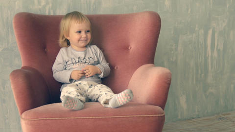 Cute little girl climbs on armchair and have fun Footage