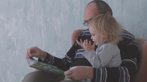 Grandfather reads a book with little granddaughter Footage