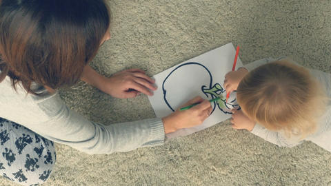 Mother with little daughter draws in album with pencils Filmmaterial