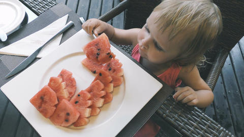 Little girl eats sliced watermelon Footage