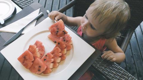 Little girl eats sliced watermelon Filmmaterial