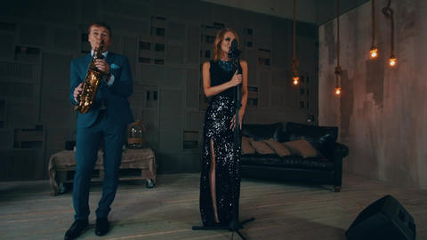 Jazz vocalist in glowing dress perform on stage with saxophonist. Live concert Footage