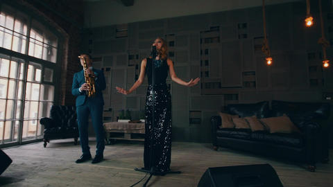 Jazz vocalist in glowing dress performing on stage with saxophonist. Raise hands Footage