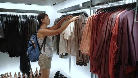 Woman looking at clothes in clothes store Live Action