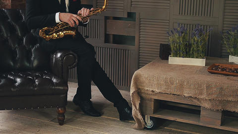 Saxophonist in dinner jacket sit on chair with golden saxophone. Jazz musician Footage