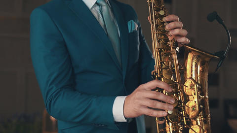 Saxophonist in blue suit playing on golden saxophone at stage. Elegance. Jazz Footage