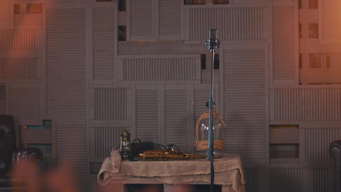 View of stage with studio microphone, table with saxophone, jar. Spotlights Live Action