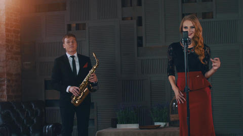 Jazz duet perform on stage. Saxophonist. Vocalist click fingers at microphone ビデオ