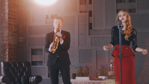 Jazz duet on stage. Saxophonist playing. Vocalist sing and click fingers ビデオ