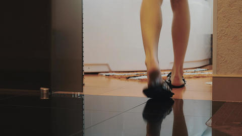 View of young woman in funny slippers walk to bathroom and sit down on bath Live Action