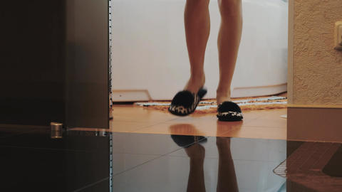View of young woman in slippers stand up from bath and walk out bathroom Live Action