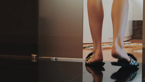 Woman in slippers walk into bathroom open door and sit on bath. Legs Live Action