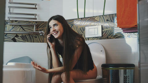 Brunette girl sitting on toilet emotionally talking on phone. Bathroom. Laugh Footage