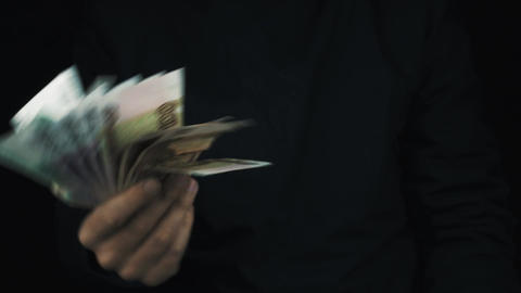 Male hand in long sleeve jacket shaking pile of money bank bills in air as fan Footage