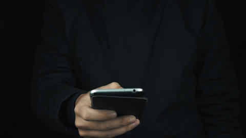 Male hand in long sleeve jacket using cased silver smartphone with thumb Footage