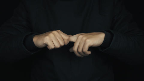 Male hands in long sleeve jacket pull cracking fingers in turn one by one Footage