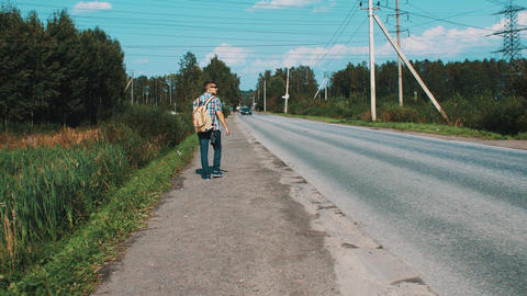 Boy with backpack walking along roadside. Hitchhiking. Traveler. Cars. Summer Footage