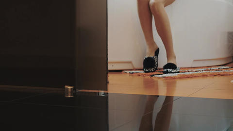 View of young girl in slippers stand up from bath and walk out bathroom Live Action