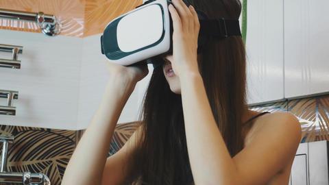 Girl sitting in bathroom looking in virtual reality glasses. Modern gadget Footage