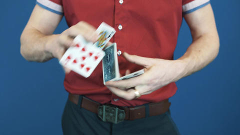 Close up conjurer in red shirt shuffle playing cards, show Queen of Spades Footage