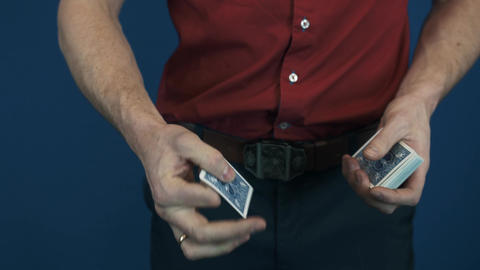 Close up illusionist in red shirt showing playing cards magic focuses Footage