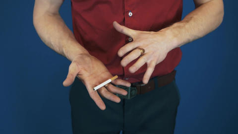 Close up illusionist in red shirt telekinesis magic focus cigarette flying Footage