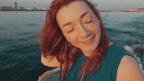 Red hair girl in turquoise dress sail on motor boat. Beautiful sunset. Relax Footage
