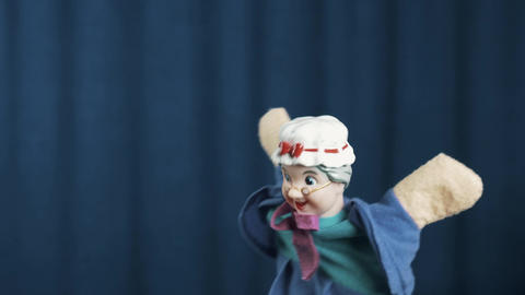 Old woman hand puppet appears on scene smooth dance movements on blue background Live Action