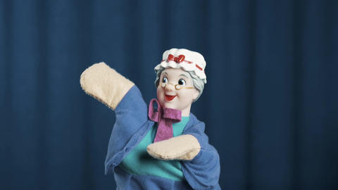 Old woman hand puppet appears on scene make tossing movements on blue background Live Action