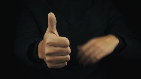 Male hand in long sleeve jacket make positive thumbs up finger gestures Footage