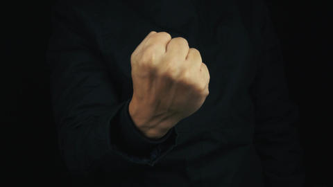 Male hand in long sleeve jacket pulling fist up, make threating sign gesture Footage