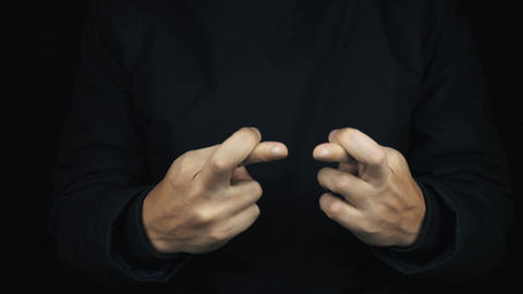 Male hand in long sleeve jacket making cross fingers hope sign gesture Footage