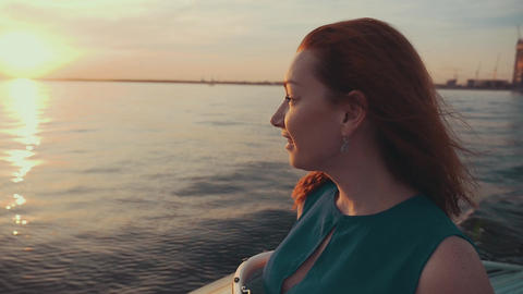Red hair happy girl in dress on motor boat. Beautiful sunset. Entertainment Footage
