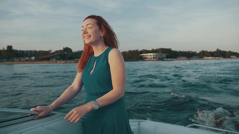 Happy red hair girl in turquoise dress dance on motor boat. Shake hair. Laugh Footage