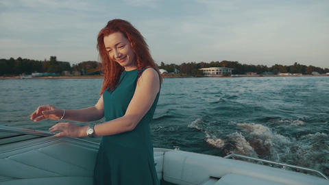 Happy red hair girl in turquoise dress on motor boat. Touch hair. Fun. Smile Footage
