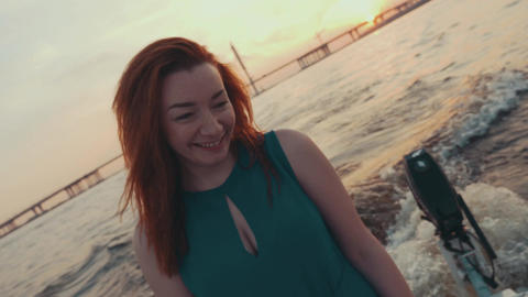 Young girl in turquoise dress touch hair on sailing motor boat. Sunset. River Footage