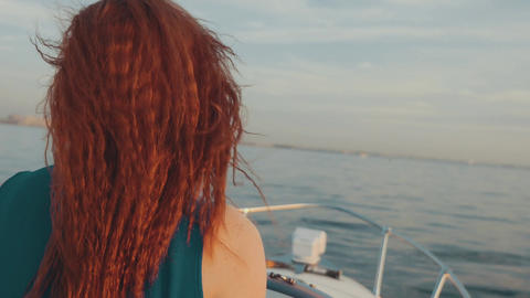 Happy red hair girl in turquoise dress steer motor boat. Beautiful sunset Footage