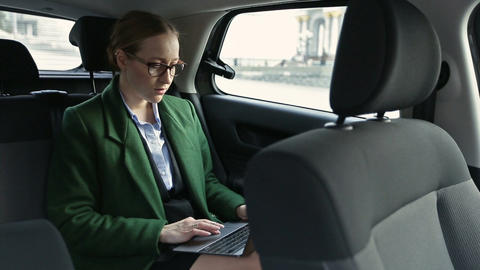 Serious businesswoman working in car on laptop Footage
