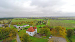 Old castle with red roof. Autumn nature landscape. Camera around.Aerial footage Footage