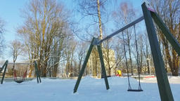 Walk along the city covered with snow. Kids playground. Sunny winter day