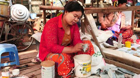 Middle age woman polishing a piece of jade in Mandalay jade bazaar in Myanmar Footage