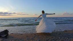 Beautiful bride spinning around on beach in sunset Footage