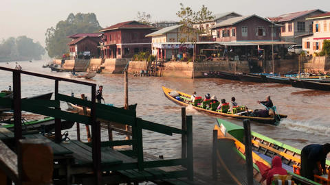 jetty with people and traditional boats in river - Myanmar, Inle lake channel at Footage