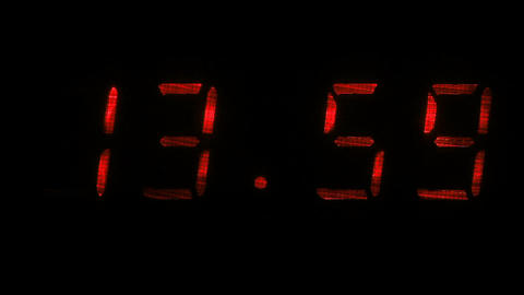 Digital clock shows the time of 13 hours 59 minutes to 14 hours 00 minutes Footage