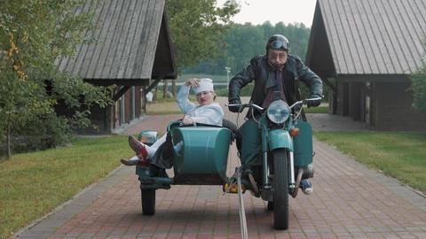 Biker with tie ride motorcycle with woman nurse costume grimacing in sidecar Footage