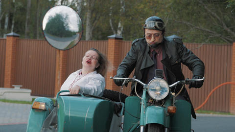 Biker ride in suburbs motorcycle with woman nurse costume grimacing in sidecar Footage