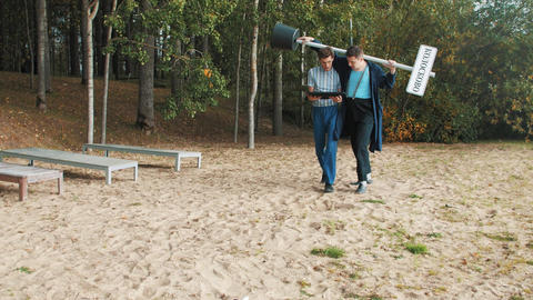 Two men with city sign walking on sandy beach looking into monitor tablet Footage