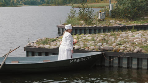 Woman in nurse costume and man in white coming out boat at pier on sunny day Footage