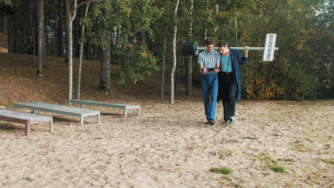 Two guys with city sign walking on sandy beach looking into monitor tablet Footage