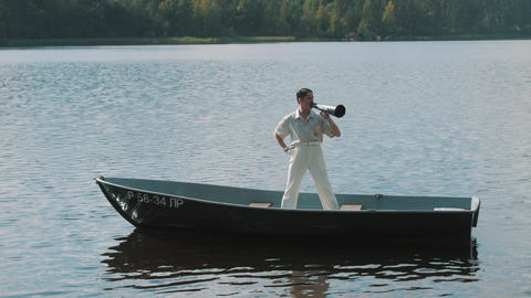 Man in hair net and white clothes standing on boat yelling into megaphone Footage